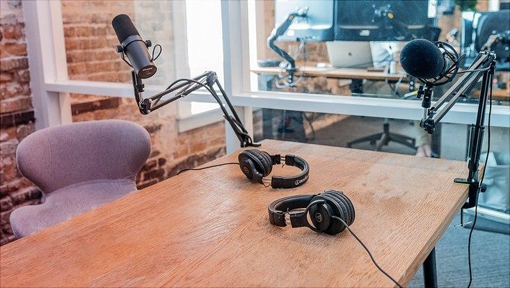pocast szenerie mikrofone bildschirme und headsets liegen auf schreibtischen