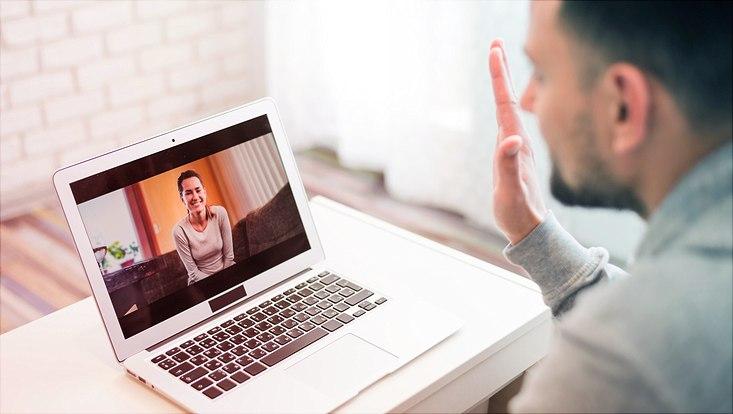 Das Bild zeigt einen jungen Mann beim Onlinetreffen mit einer jungen Frau.