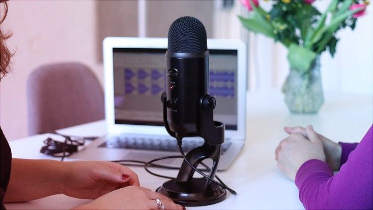 Interviewsituation zwischen zwei frauen mit einem laptop und einem mikrofon auf dem tisch