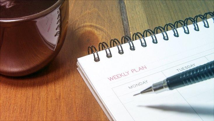 Das Bild zeigt einen aufgeschlagenen Kalender neben einer schwarzen Tasse.