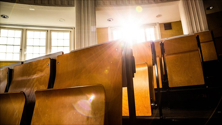 leere Stuhlreihen in einem Hörsaal, durch ein Fenster scheint ein Sonnenstrahl