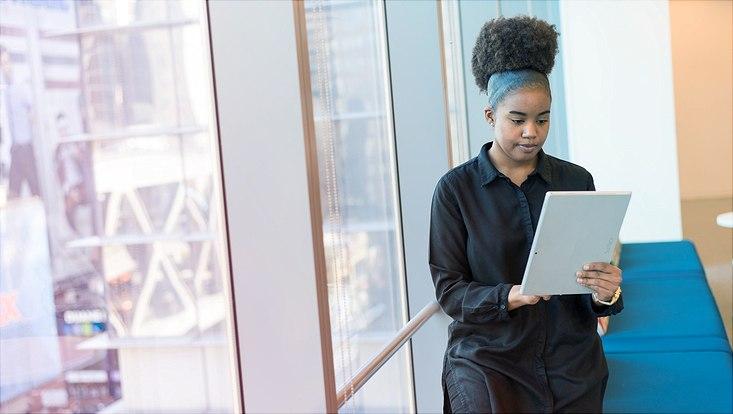 Das Bild zeigt eine junge Frau beim Lesen in einem E-Reader.