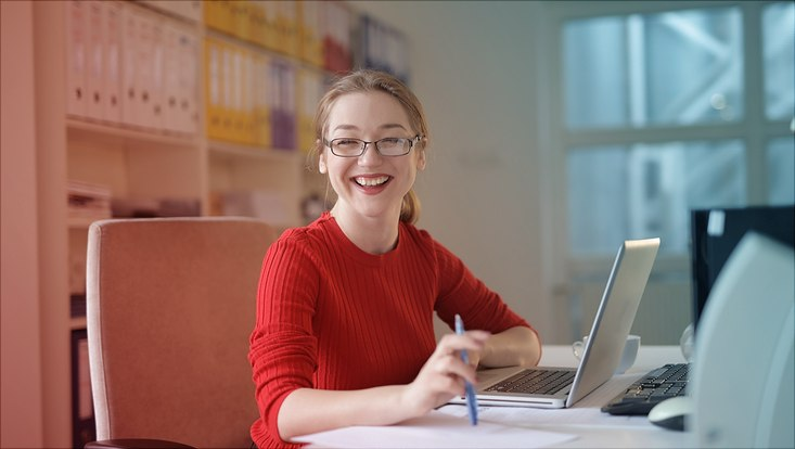 Das Bild zeigt eine fröhliche junge Frau am Schreibtisch in einem Büro mit einem aufgeklappten Laptop vor sich.