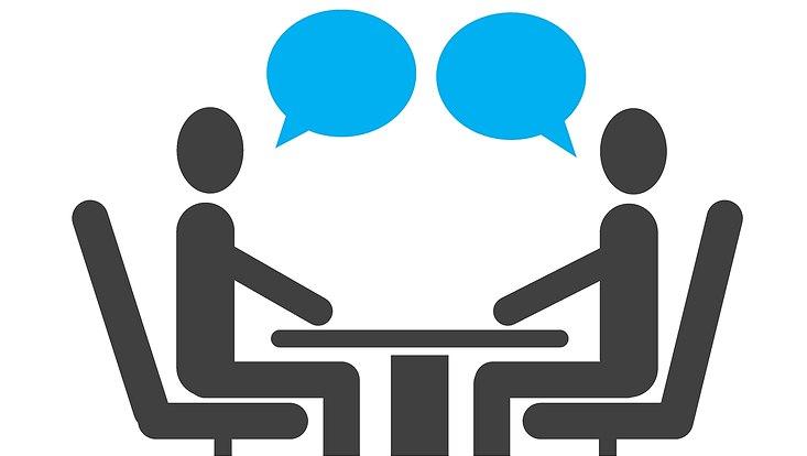 Zeichnung: zwei Menschen, dargestellt durch Strichmännchen, sitzen an einem Tisch, über ihnen jeweils eine Sprechblase