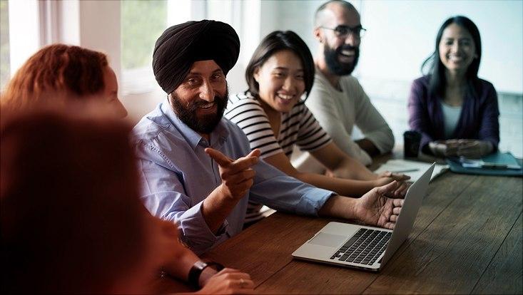 Das Bild zeigt eine Gruppe von Menschen unterschiedlicher Religionen im freundlich-angeregten Gespräch.