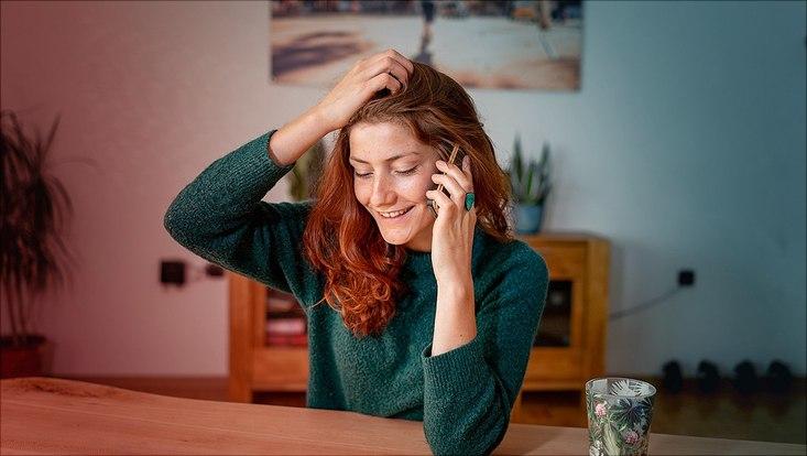 Das Bild zeigt eine junge mit dem Smartphone telefonierende Frau.