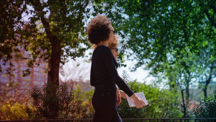 Das Bild zeigt eine durch einen Park gehende junge Frau mit einem Buch in der Hand.