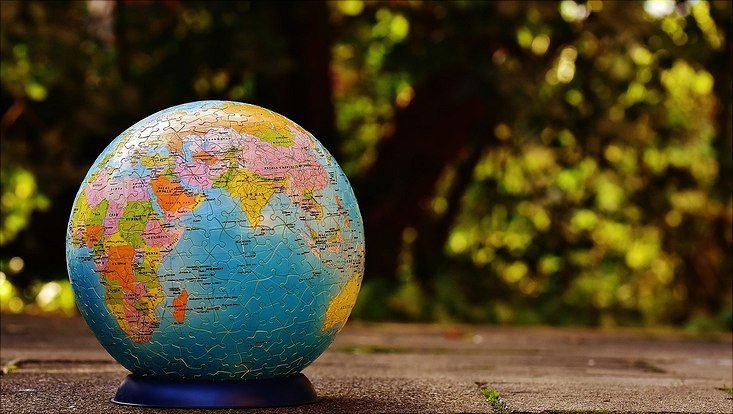 Eine Weltkugel als Puzzle Ball liegt auf einer Wiese.