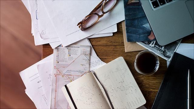 Das Foto zeigt einen unordentlichen Schreibtisch mit vielen Büchern und Zetteln sowie eine Notebook und einer Kaffeetasse darauf.