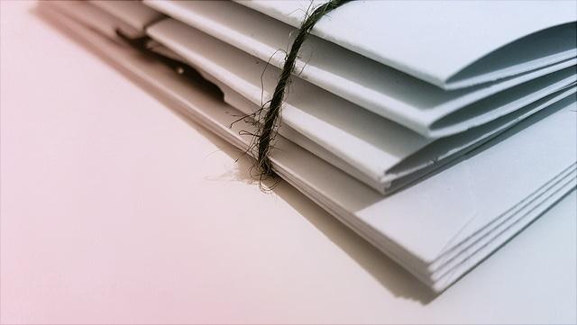 Das Bild zeigt einen haufen Papier mit einem Wollfaden umbunden