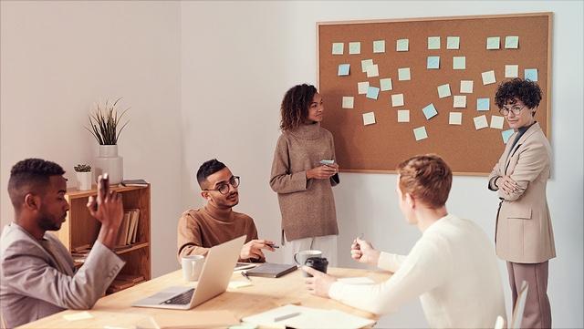Fünf Personen brainstormen und tragen Ergebnisse an einer Pinnwand zusammen.