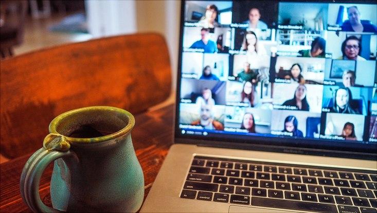 Das Bild zeigt einen aufgeklappten Laptop mit Teilnehmenden einer Zoom-Konferenz auf dem Bildschirm.