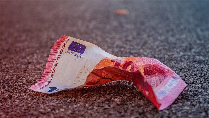 Ein zerknitterter Geldschein auf dem Boden