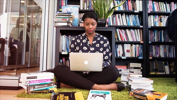 Frau sitzt im Schneidersitz auf dem Boden mit Laptop auf dem Schoß und ist von vielen Büchern umgeben