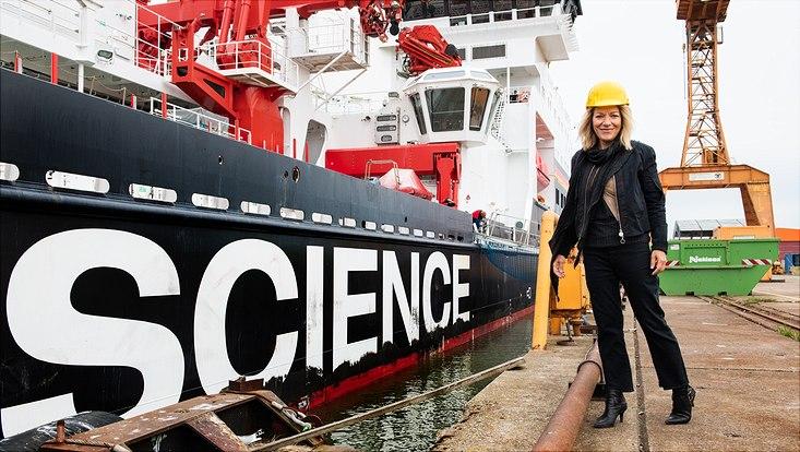 """Antje Boetius steht vor einem Schiff mit der Aufschrift """"Science"""""""