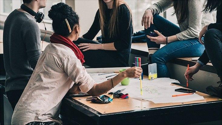 Jugendliche sitzen um einen Tisch herum auf dem Schreibmaterialien liegen und arbeiten zusammen.