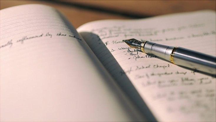 Ein aufgeschlagenes Buch in dessen Mitte ein Füller liegt.
