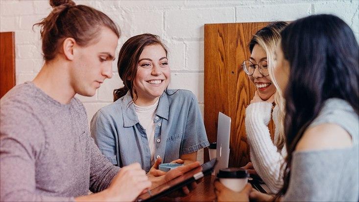 Das Bild zeigt eine Gruppe junger Menschen im Gespräch.