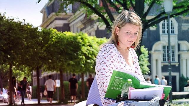Studentin sitzt im Freien auf dem Campusgelände und liest ein Buch.