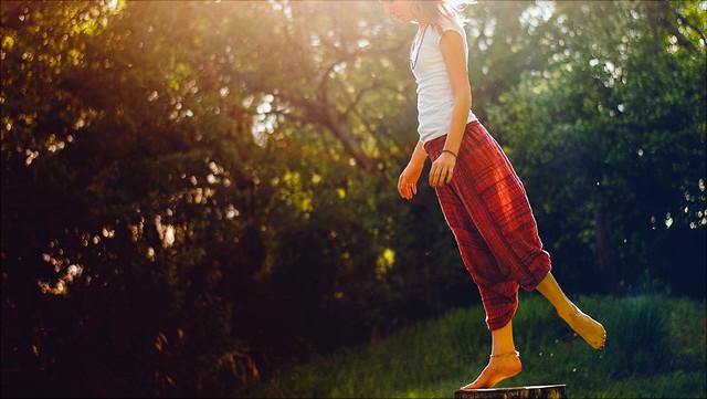 Frau balanciert mit einem Bein auf Baumstumpf