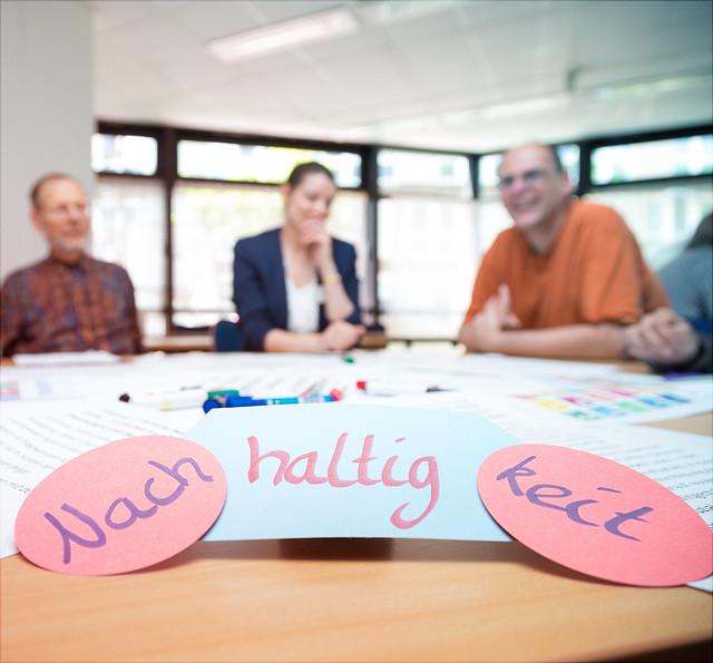 Moderationskarten mit Schriftzug Nachhaltigkeit, Menschen im Hintergrund