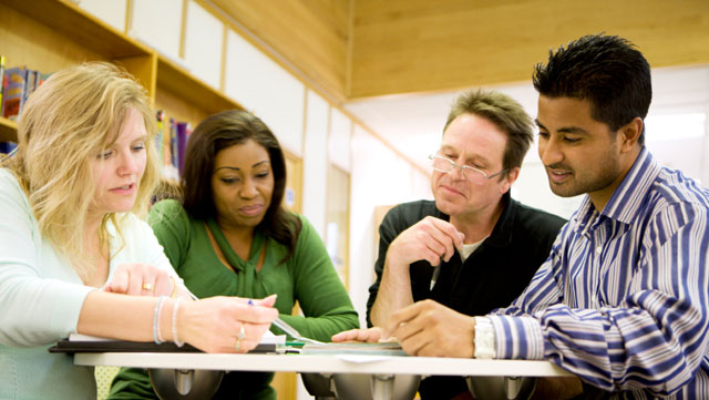 View from slightly below two women and two men of different age and skin color looking together at documents on a table.