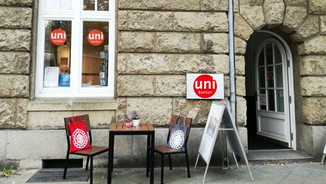 View of the outside entrance of the UHH university account, with rustic masonry. In front of the window two chairs decorated with fabric bags, a table in the middle and a poster stand on the right.