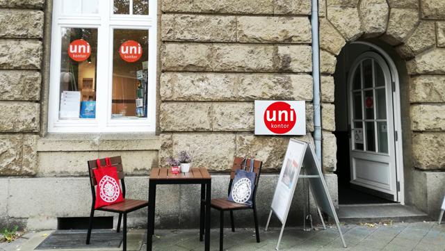 Blick auf den Außeneingang des Unikontos der UHH, mit Rustika Mauerwerk. Vor dem Fenster zwei Stühle mit Stoffbeuteln dekoriert, ein Tisch in der Mitte und rechts daneben ein Plakatständer.