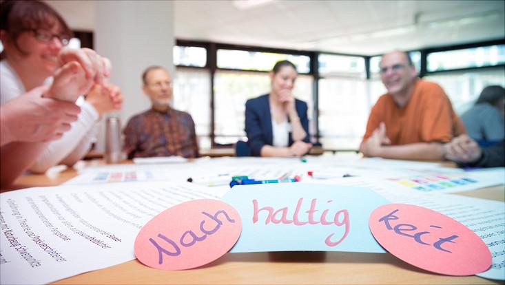 Vordergrund: Schriftzug Nachhaltigkeit; Hintergrund: Diskutierende Menschen an Tisch