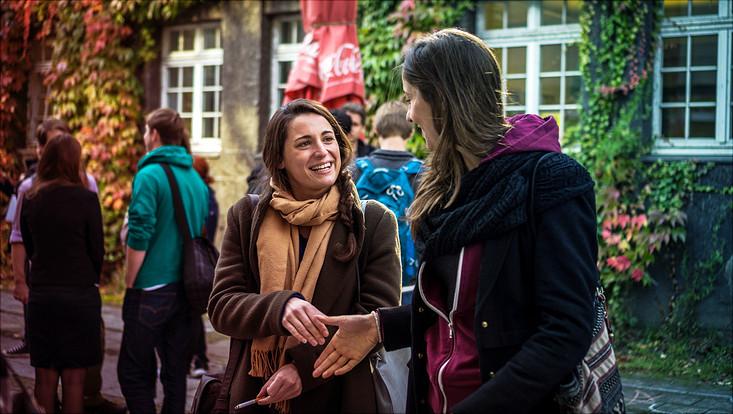 2 Studentinnen begrüßen sich vor Weinlaub in Studentengruppe