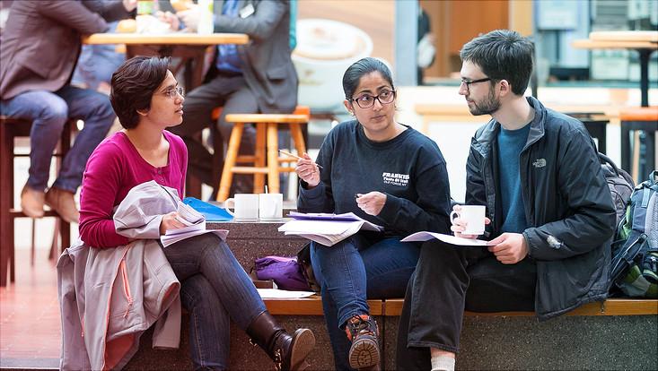 Gruppe internationaler Studierender, sitzend und diskutierend