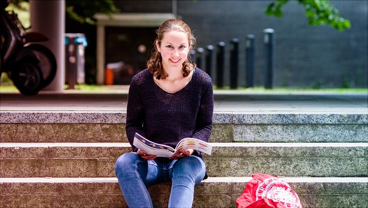 Studierende sitzt auf einer Treppe und lächelt in die Kamera