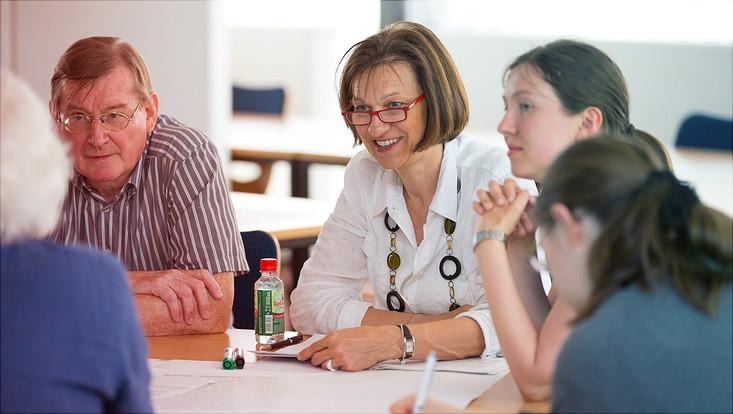 Menschen unterschiedlichen Alters sitzen an einem Tisch und diskutierend fröhlich