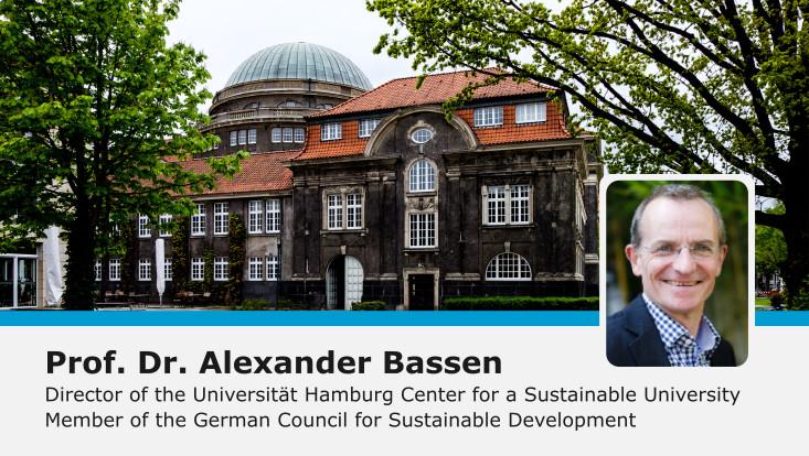 Alexander Bassen eingeklingt vor Hintergrund mit Bäumen und Stele 'Kompetenzzentrum Nachhaltige Universität'
