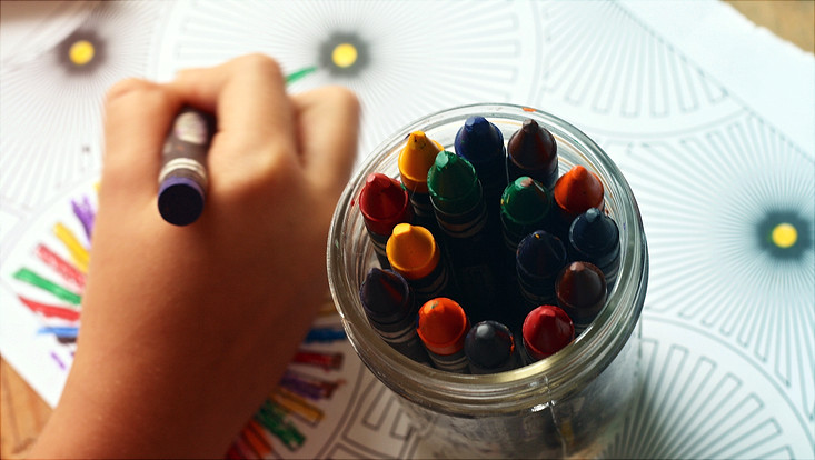 Child painting with wax crayon