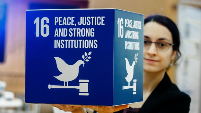 Woman holding cube with SDG 16
