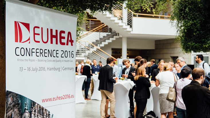 View of congress participants at bar tables, in the foreground the EUHEA standing banner, foliage at the edge of the picture and zigzag stairs in the background