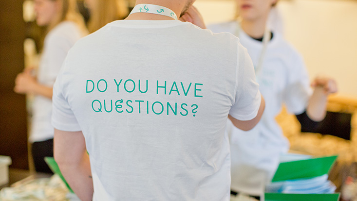 """Back of a person wearing a white T-shirt with the imprint """"DO YOU HAVE QUESTIONS?"""