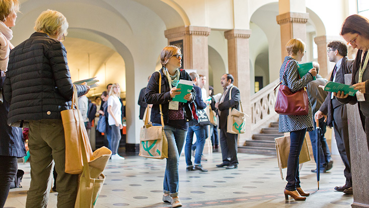 Some people and groups of people, with green notebook in hand, in the foyer of the main building of the UHH, with stairs in the background. In the center of the picture a young woman walking towards the right corner, also with a green notebook in her