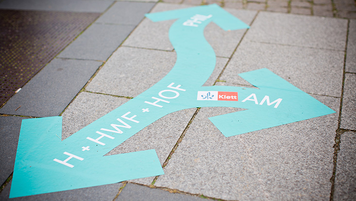 """Close-up view of stone slabs of a path on which a turquoise-green, curved arrow symbol, with three directional arrow ends is alive, on it the inscription """"H + HWF + HOF, PHIL, AM and a Klett logo."""