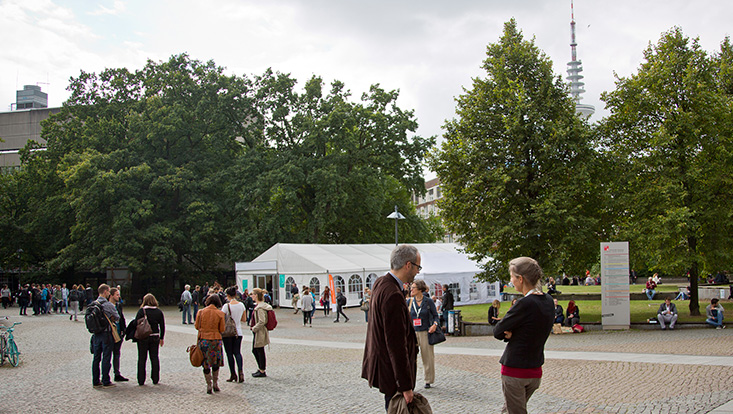 View of a paved square, with some people and groups of people, in the background a long, white event tent and trees on the right and left. In the upper right corner you can see the hamburg television tower.