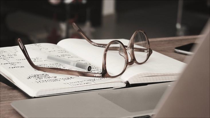 Brille liegt auf Notizbuch