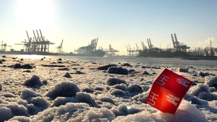 UHH-Würfel auf Eis im Vordergrund, Hafen im Hintergrund