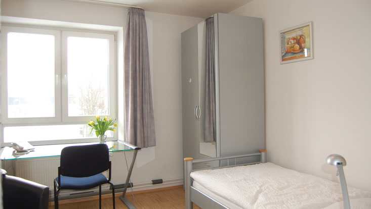 Room with bed, picture on the wall, curtains, closet with mirror and glass desk and chair in front of the window