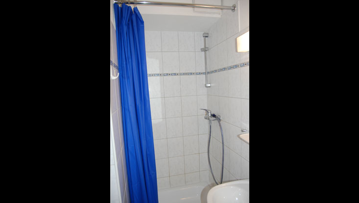 Tiled bathroom with blue shower curtain, towel hook and wash basin