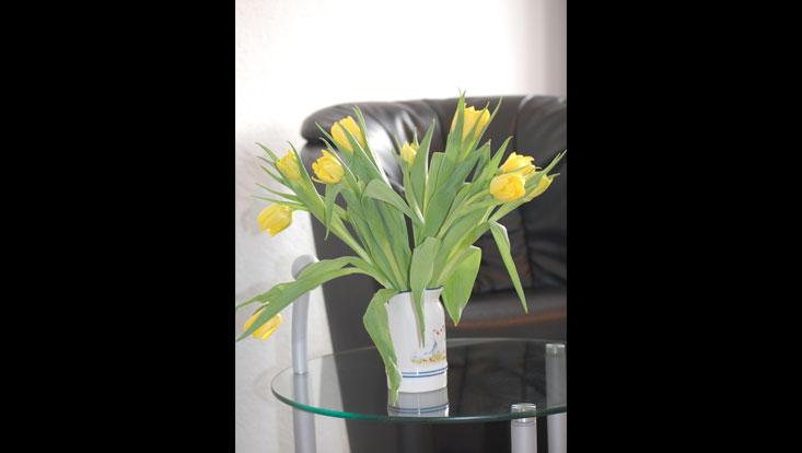 Vase mit gelben Tulpen auf kleinem, runden Glastisch, im Hintergrund ein schwarzer Ledersessel