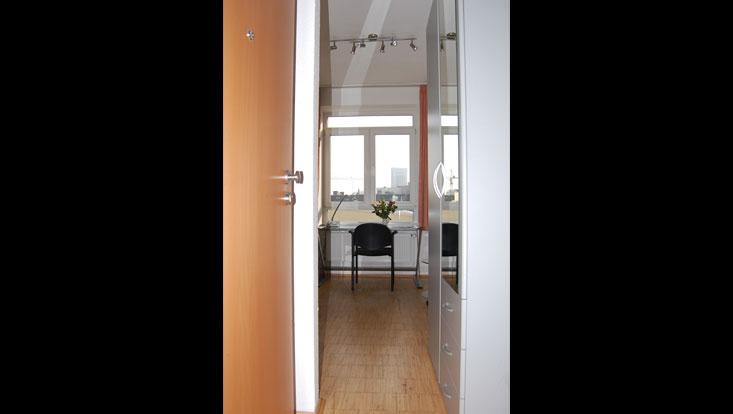 Blick durch den Raum, direkt auf das Fenster mit Glasschreibtisch und Stuhl davor (Ansicht von der Kochnische)