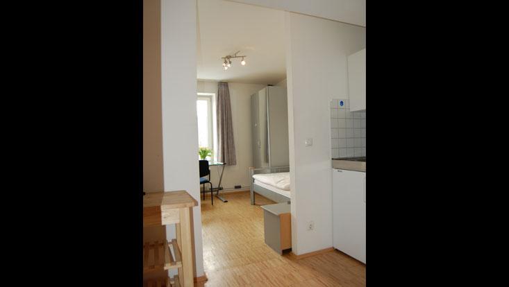 Raum mit Gardinen, Glasschreibtisch vor dem Fenster, Bett und Schrank mit Spiegel (Ansicht von der Kochnische)