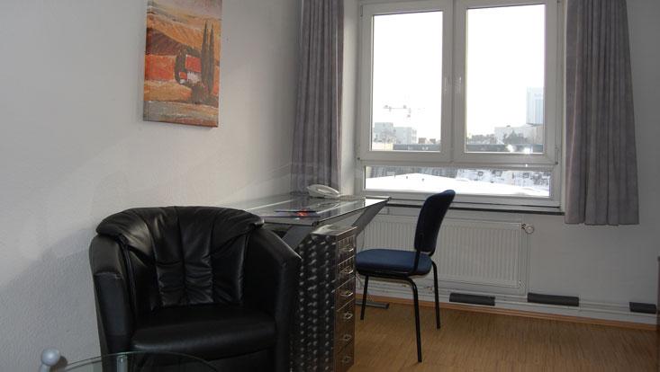 Raum mit Gardinen, Ledersessel, Glasschreibtisch mit Schubladencontainer und Stuhl beim Fenster