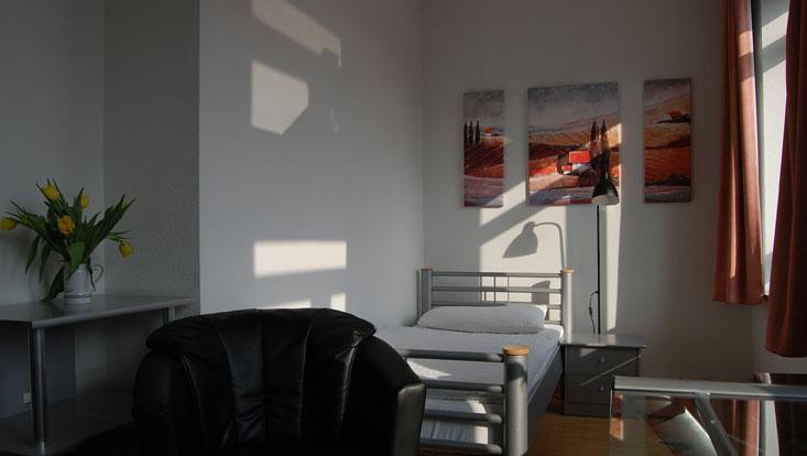 Raum mit Bett, Bildern über dem Bett, Blumen, Sessel, Gardinen und Lichteinfall durchs Fenster